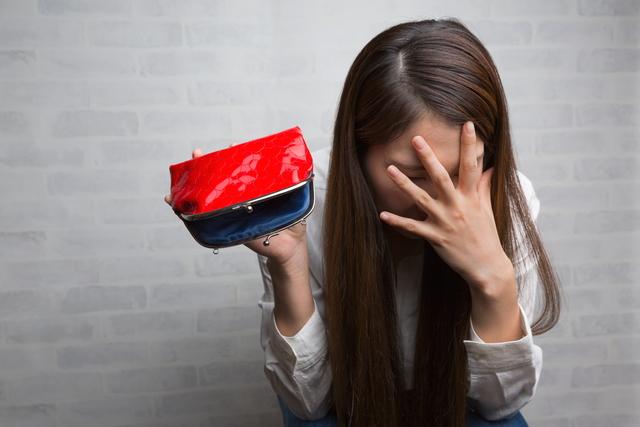 空っぽの財布に悩む女性