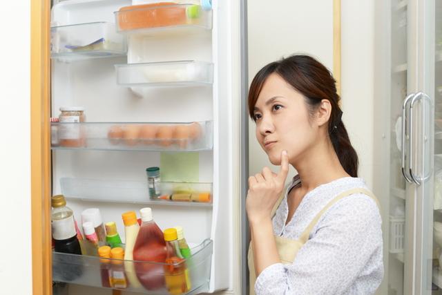 冷蔵庫の前で考える女性