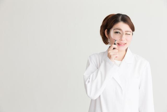 虫メガネで覗く女性