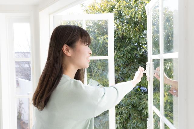 窓を開けて換気する女性