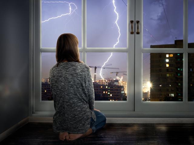 家の中から雷を見る女性