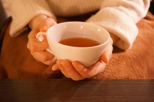 紅茶の入ったカップを持つ女性