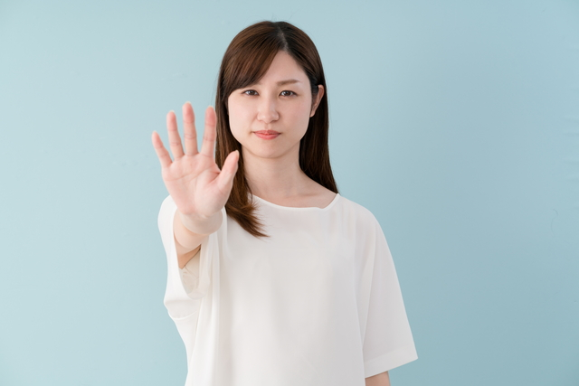 手を広げて警告する女性