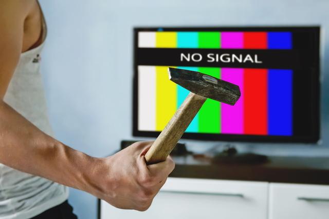 壊れたテレビとハンマーを持つ人