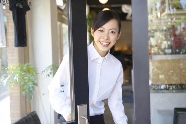 店のドアを開ける女性
