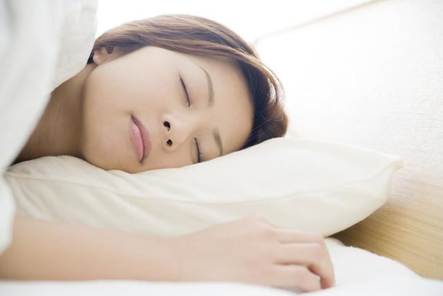 布団乾燥機にかけた布団で寝る女性