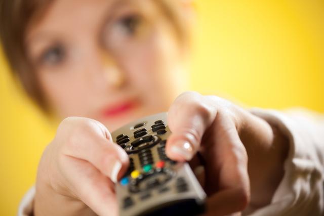 テレビのリモコンを持つ女性
