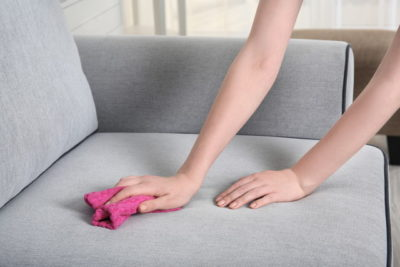 ソファーを掃除する女性