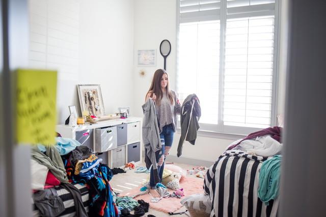 汚い部屋の中で立っている女性
