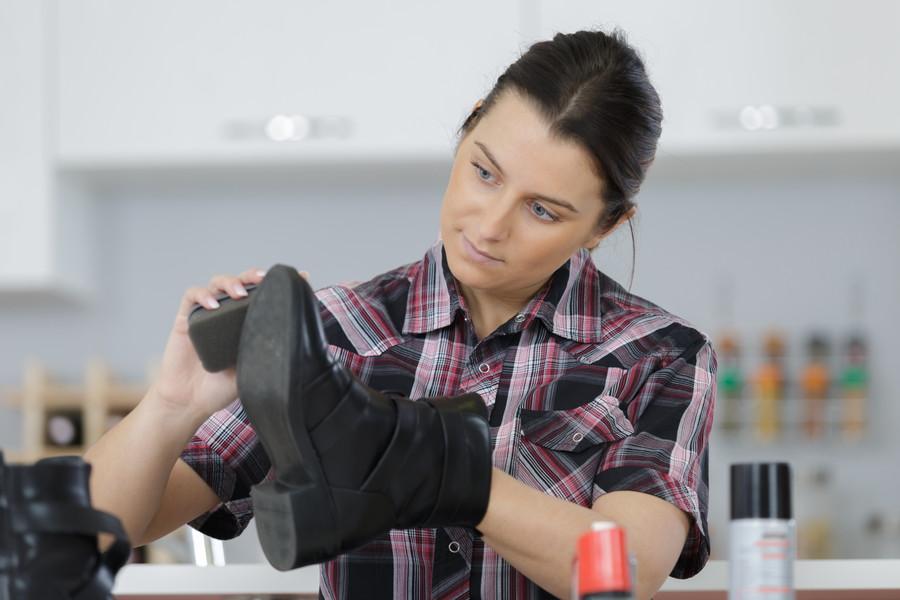 革靴の手入れをする女性