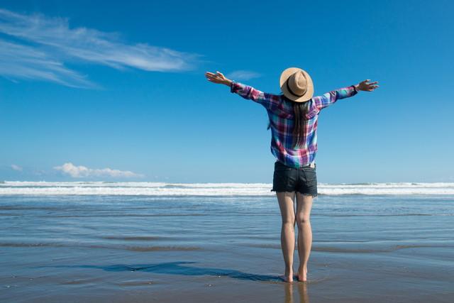 海辺で深呼吸をする女性