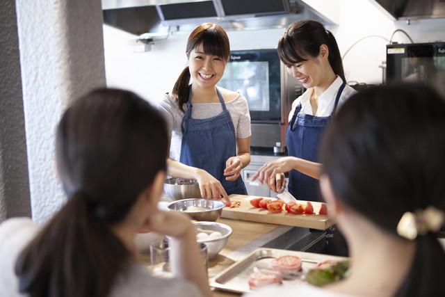 料理教室で講師の説明をうける女性