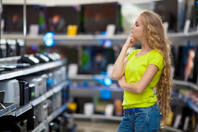 家電量販店で悩む女性