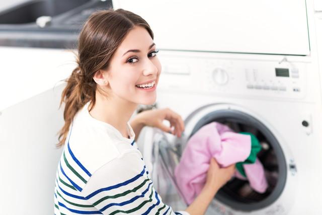 ドラム式洗濯機で洗濯する女性