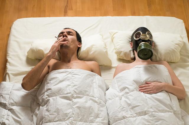 寝室でタバコを吸う夫とガスマスクをする妻