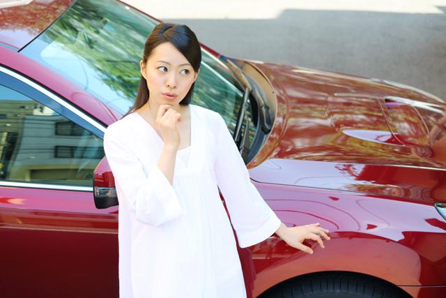 車の横で考える女性