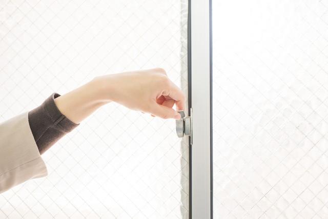 窓がカギに触れる女性の手
