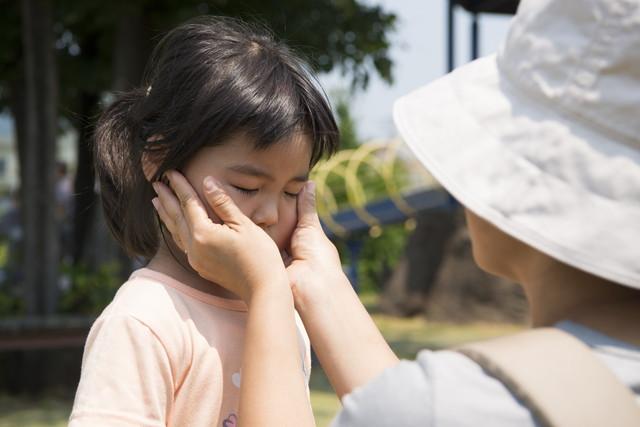 子供の顔に日焼け止めを塗る母親