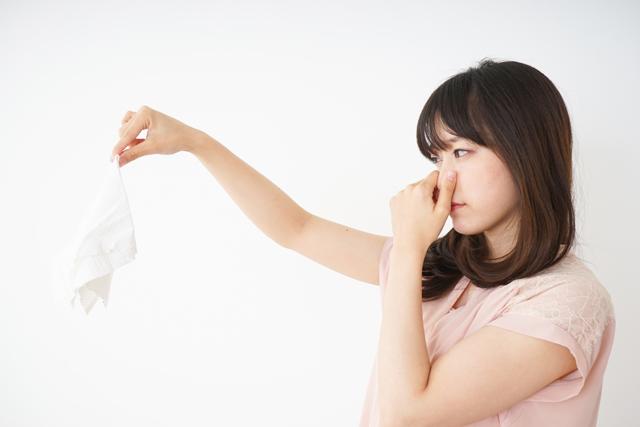 タオルの臭いで鼻をつまむ女性