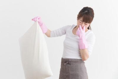 枕の臭いで鼻をつまむ女性