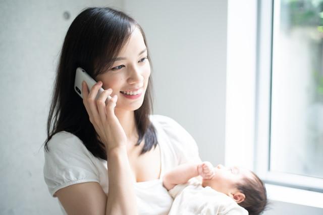 赤ちゃんを抱きながら携帯電話で話す女性