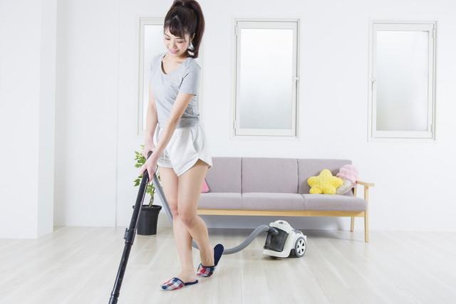 ソファーの前で掃除機をかける女性