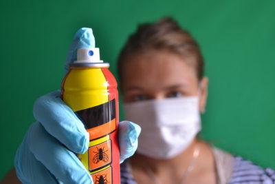 マスクを着ている女性と殺虫剤