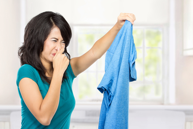 洗濯物の悪臭で鼻をつまむ女性