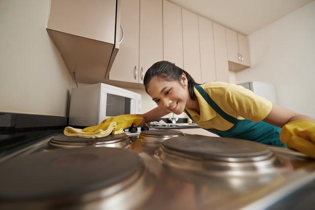 電気コンロを掃除する女性