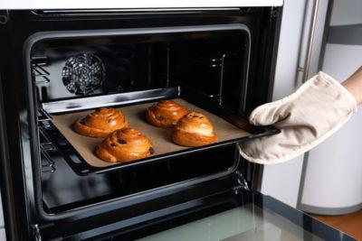 オーブンからパンを取り出す女性