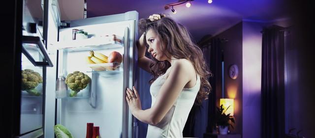 冷蔵庫を開けて悩む女性