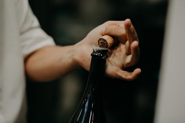 ワインのコルクを抜く人