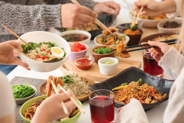 テーブルでおいしい中華料理を食べている友人
