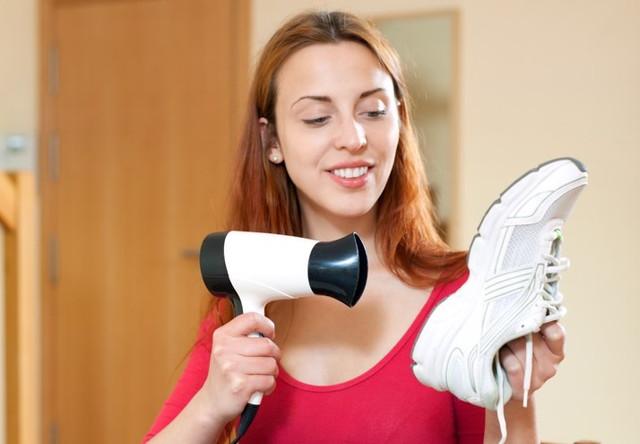 靴をドライヤーで乾かす女性
