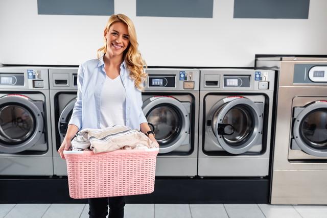 コインランドリーに洗濯物を運ぶ女性