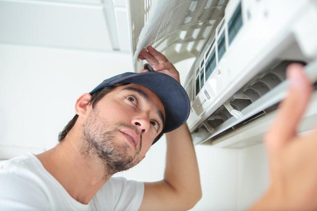 エアコンの異常を調べる男性