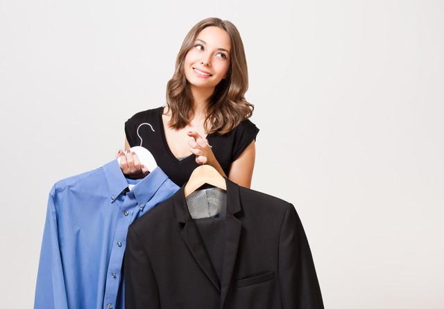 スーツを持って悩んでいる女性