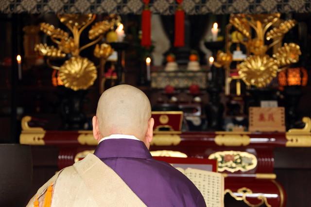 仏壇の前に座っているお坊さん