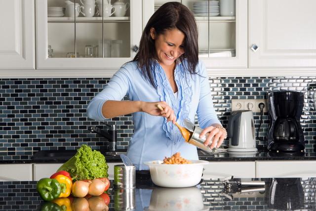 缶を使って料理をしている女性
