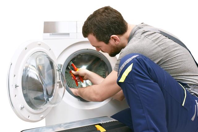 洗濯機をペンチで解体している