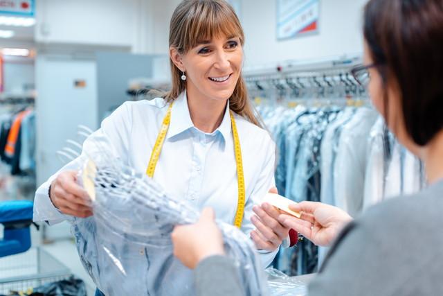 クリーニング店の店員と受け取る女性