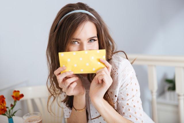 ナプキンで口元を隠す女性