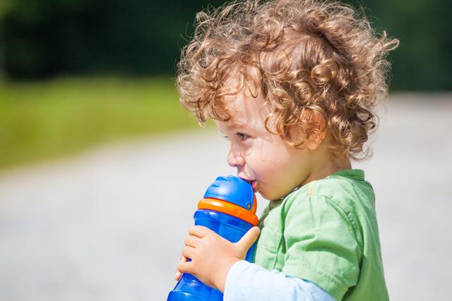 水筒で飲む子供