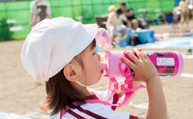 水筒で飲む女の子