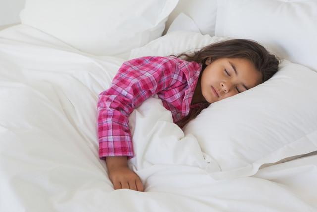 布団にくるまってすやすや眠る子ども