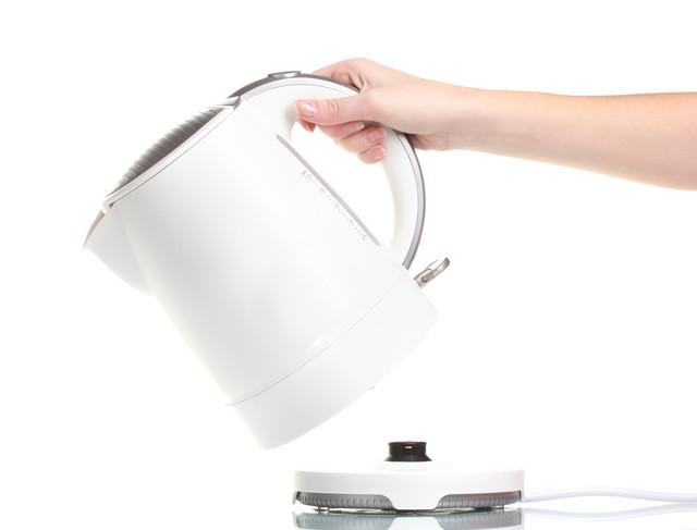 女性の手と白で隔離される白い電気ポット