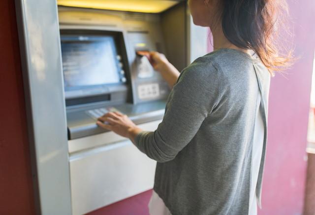 atm機にカードを挿入する女性