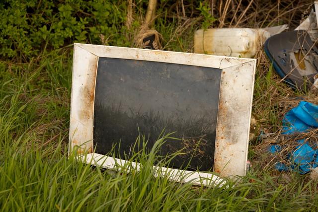 草むらに置いてある汚れたテレビ