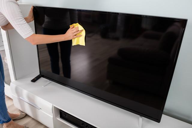 テレビをクリーニングしている女性