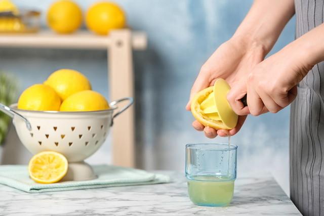 グラスにレモン汁を絞る女性